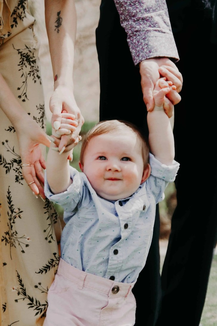 family of three holding baby's hands as he walks