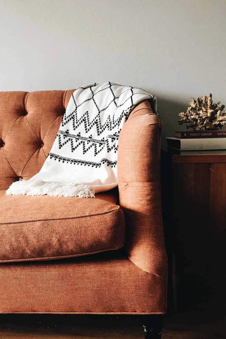 orange couch with black and white throw