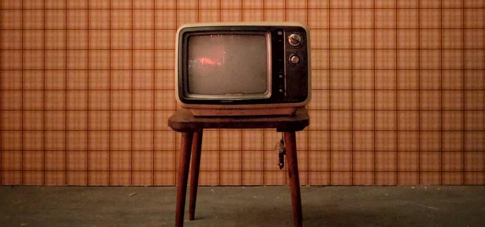Kuva vanhasta kuvaputkitelevisiosta tyhjässä tapetoidussa huoneessa puisella jakkaralla.