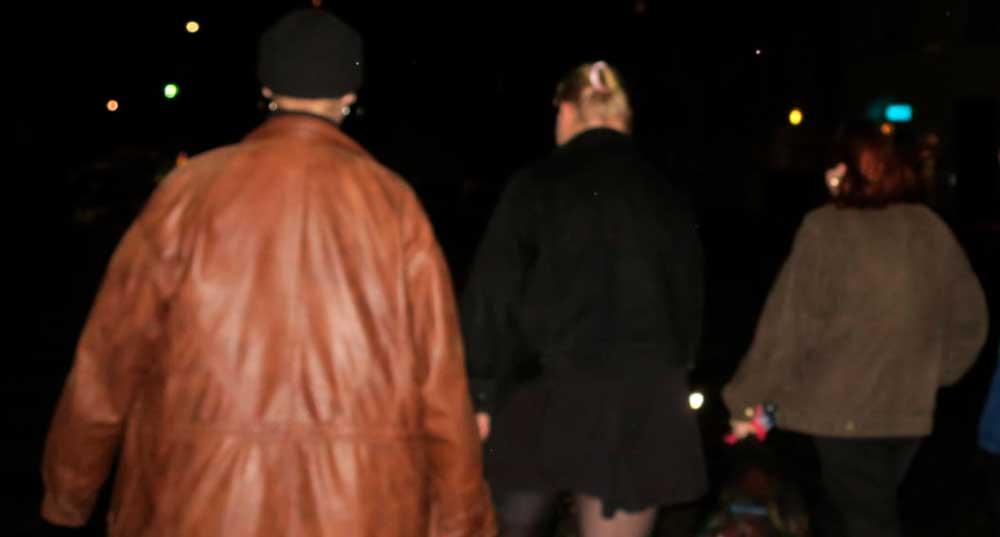 Kolmen nuoren selät kävelemässä pimeässä.