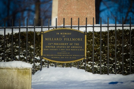 A plaque commemorating Millard Fillmore hangs on a gate in front of the grave site in Forest Lawn Cemetery.