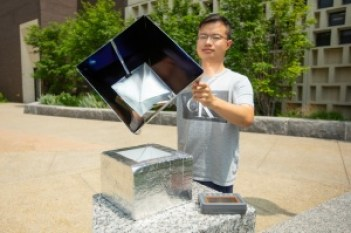 Lyu Zhou holds up a unit of the radiative cooling system, showing the interior.