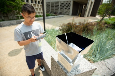 Lyu Zhou tests the radiative cooling device developed by UB researchers on top of a stone bench.
