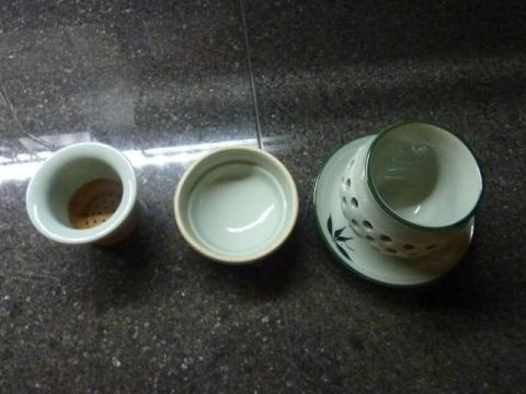 This Korean celadon tea cup set has a strainer, cover, cup and saucer.