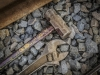 Close up photograph of a sledgehammer and large cresent wrench.