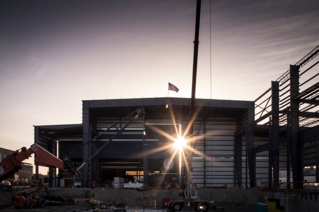 sunrise over building with American flag waving in wind