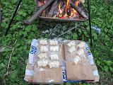 焚き火のそばでパン生地を温める