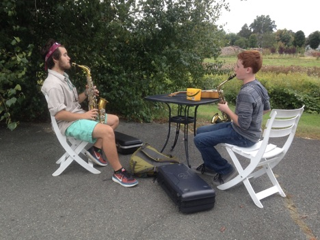 Two teen boys practicing saxophone playing outside