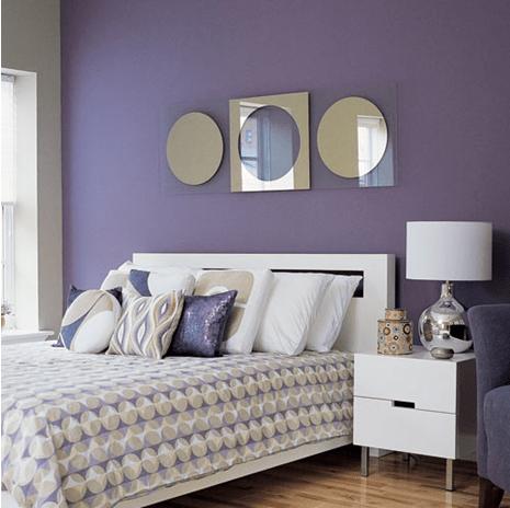 a set of artistic mirrors modern headboard on a lavender wall