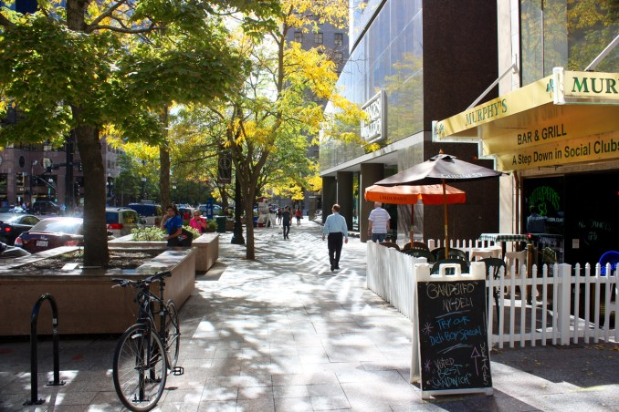 Active streetscapes require various uses that engage pedestrians. Trees and seating areas offer shade and rest. Photo by Isaac Riddle.