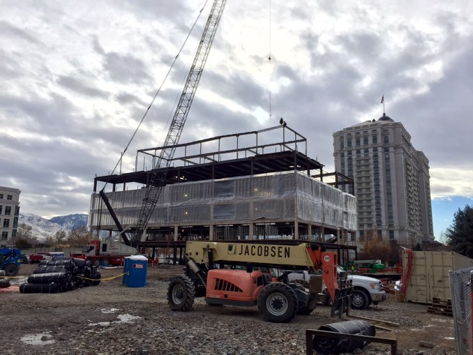 A worker puts the final steel beam into place.  Photo by Isaac Riddle.
