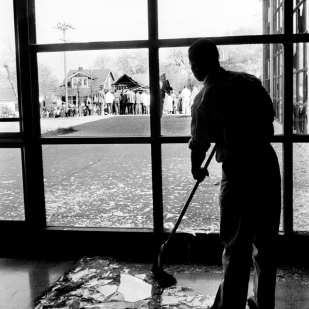 Silhouetted against disaster, John Thomas Martin wields his broom, sweeping up the fragments of glass from shattered windows in the Meharry Medical College Alumni building April 19, 1960. In the background, a curious crowd gathers at the bombed home of Z. Alexander Looby, which shattered 147 windows at the college. Joe Rudis for The Tennessean