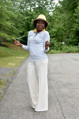 I am ready for summer in my feather earrings and wide legs pant outfit. graphic