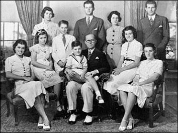 Господин и Госпожа Джоузеф П. Кенеди с техните 9 деца в Бронксвил, щата Ню Йорк 1938 година. От ляво на дясно: седнали: Юнис (Eunice), Джийн (Jean), Едуард (Edward (седнал на коляното на татко си), Патриша (Patricia), и Катлийн (Kathleen). Прави: Роузмари (Rosemary), Роберт (Боби, Robert), Джон (Дж.Ф.К. John), Г-жа Кенеди (Kennedy) и Джоузеф Джуниър (Joseph, Jr.) ФОТО: Фондация СИБИЛИНГ СЪПОРТ