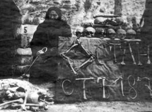 """Марга Горанова, съпруга на водача на въстанието в Батак - Никола Горанов. С кости е изписано отстрани – """"Останки от 1876 година"""".Снимката е направена от учителя Койчо Христов Карагитлиев (1900-1989 г.) през 1927 г. След разговор с Марга Горанова той изважда кости от костницата към черквата, измива ги и ги подрежда за снимката, за да увековечи спомена за клането.Източник на информацията: Жени Койчева - дъщеря на Койчо Карагитлиев."""