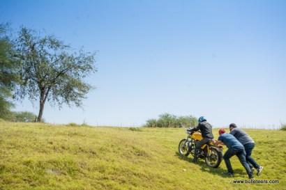 bulleteers somesh khatuja and piyush pushing mragendra atop a continental gt, up a grassy slope at pagara