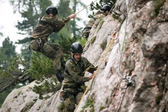 Drei Offiziere versuchen sich im Klettern an einer Felswand.