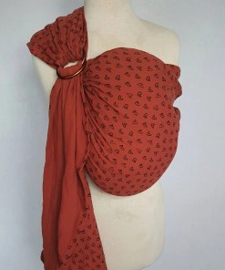 Melliapis ringsling on a mannequin in brick red with a heart print