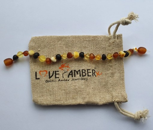 Raw mixed amber anklet laid out straight on a small hessian bag