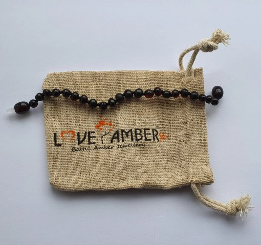 Polished cherry amber anklet laid out straight on a small hessian bag