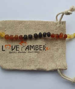 Raw rainbow amber anklet laid out straight on a small hessian bag
