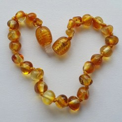 Polished honey amber anklet arranged into a heart