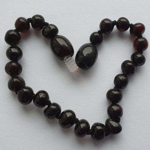 Polished dark cherry amber anklet arranged into a heart