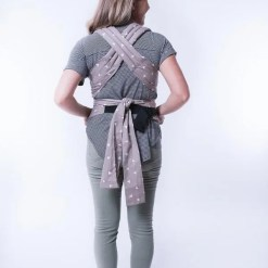 Photo of a woman carrying a baby in a sling, with straps crossed on her back tied in a knot