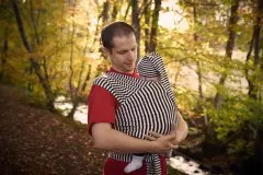 Man looking down at baby in a stripy stretchy wrap