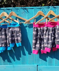 Row of grey rhino lounge pants against a blue fence