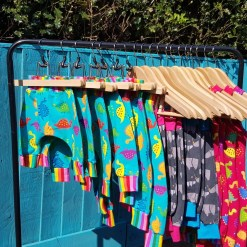Collectionn of Nell Makes clothing on a rail against a blue fence