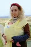 Woman carrying baby in a lemon stretchy wrap