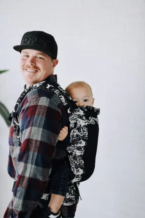 Man carrying a baby on his back in a black and white marbled Tula FTG