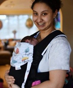 Smiling woman carrying a newborn in a Mamaruga Zensling Black Wolf