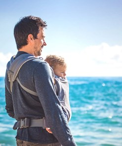 Man looking away from the camera carrying a toddler in a Beco COOL Grey Toddler with crossed straps at the back