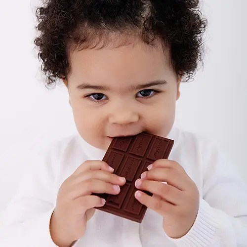 Toddler chewing on the Jellystone chocolate bar teether toy