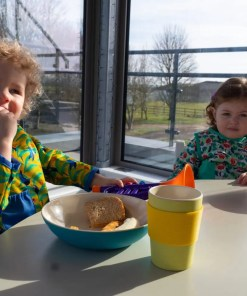 Two children enjoying breakfast wearing their Close Pop-in stage 3 coverall bibs