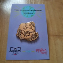 rose gold coloured pin with the words Cloth Bum Mum, on a purple card backing