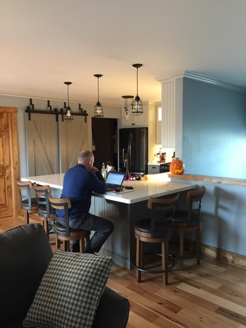 Our design removed the 1/2 wall, created an eating/work counter for 5, with a seamless, quartz counter from the kitchen side to the barstool side. This area was delineated with pendant lights over the work counter.