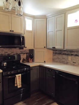 We incorporated more cabinet space and better lighting, with two tiers of cabinets and a corner cabinet with appliance storage. The upper tier has LED lighting for display, and under-cabinet LEDs light up the work surface.