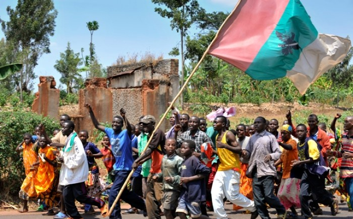 Political party members march to a rally, going past a home destroyed in the conflict in Burundi. Many fear political tensions could lead to more violence.