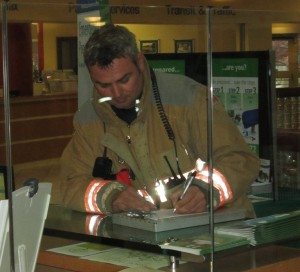 Burlington firefighter does his paper work for what turned out to be a non event when the fire alarms went off at city hall.
