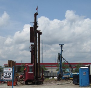 Drilling rig that bores into the ground for the pipes that will be used to carry heat into the building.  Heat exchangers convert the heat into cool air during the summer months.