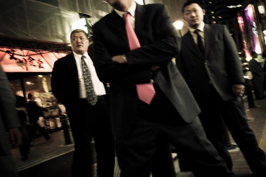 Members of the Odo family pose in the streets of Kabukicho, the red light district in the heart of Shinjuku, Tokyo, Japan. By always wearing tailored suits, the Yakuza attempt to spread an image of decency and conformity. But the underlying tension unmistakibly remains. Obvious influences are American gangster icons from the early 20th century, like John Dillinger - 2009