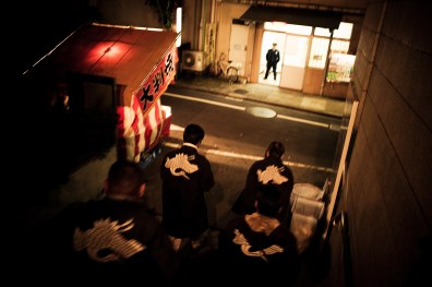 "Family members dress in uniform and patrol the yearly festival ""Sanja Matsuri"", keeping the peace amongst the many visitors. In the distance a police officer in his station watches over - 2009"
