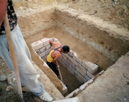 A local man digs a grave for his uncle at the Koshkar-Ata cemetery. Employing people to dig and construct graves is an expensive business, so many locals who do not have money from oil or land, have to do it themselves.