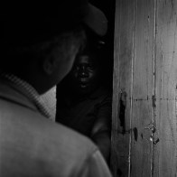 A woman opens her door in Diepsloot