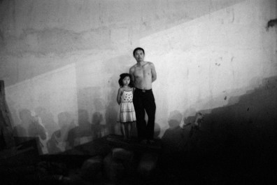 Father and daughter watch a migrant stage troupe's outdoor performance of traditional Peking Opera in Zhangjiajie, China 2005.