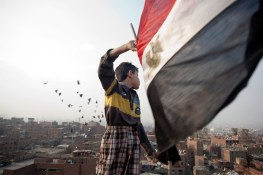 A young boy waves egyptian flag on the top of a pigeon house in moquattam mountain