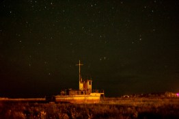 An abandoned fishing boat rests in a field in Fort Chipewyan.